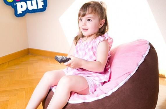 Niña sentada en puf ve la tv
