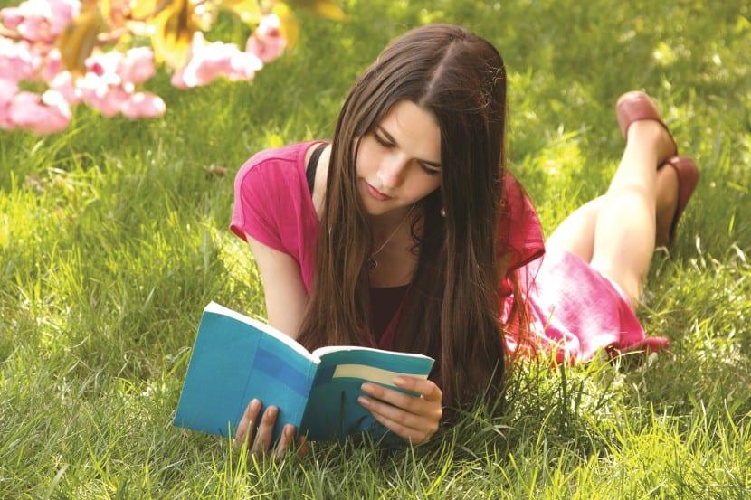 adolescente leyendo cesped