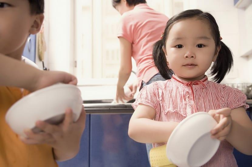 niña responsable lavando un plato