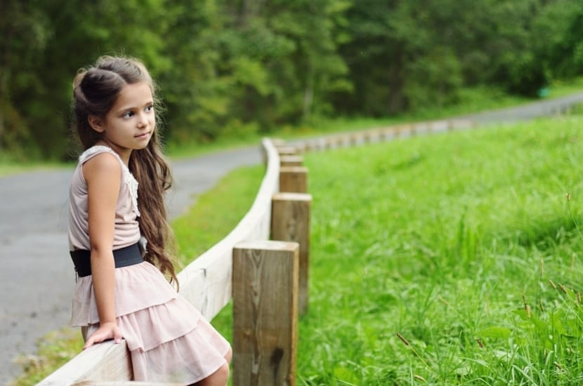 niña responsable sentada en una valla
