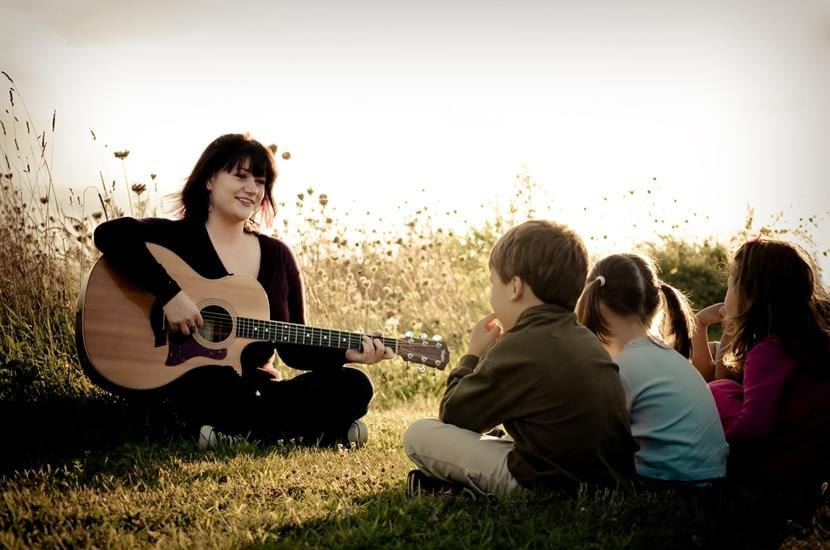 mujer tocando la guitarra para los niños