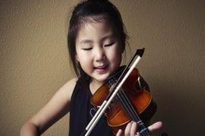 niña tocando instrumento disfrutando de la música