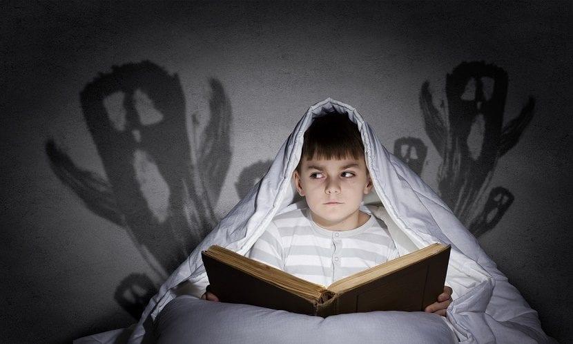 niño leyendo libro de miedo