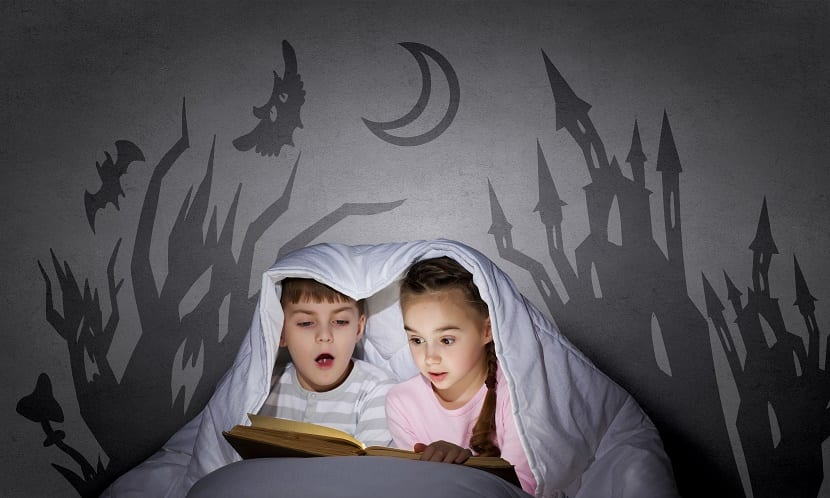 dos niños leyendo libro de miedo