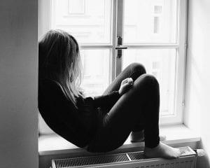 Chica sentada al lado de la ventana