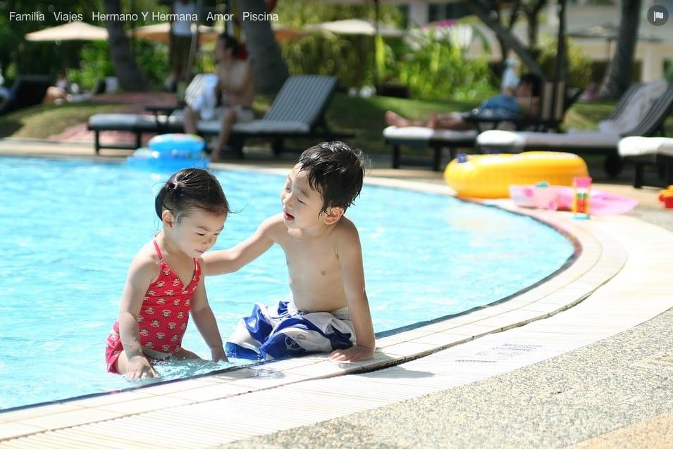 Niños jugando al borde de la piscina.