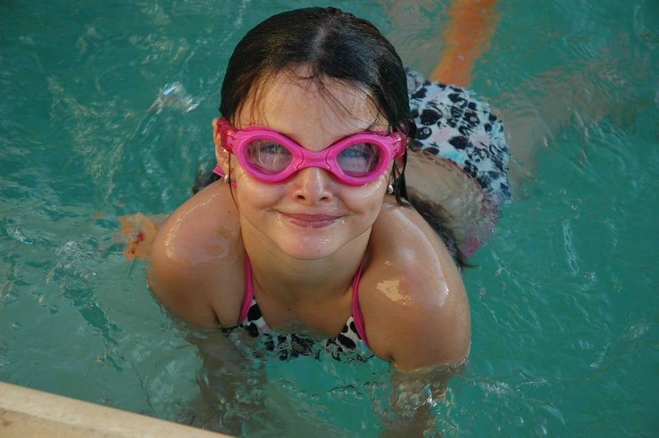 Niña con gafas de sol nadando en la piscina.