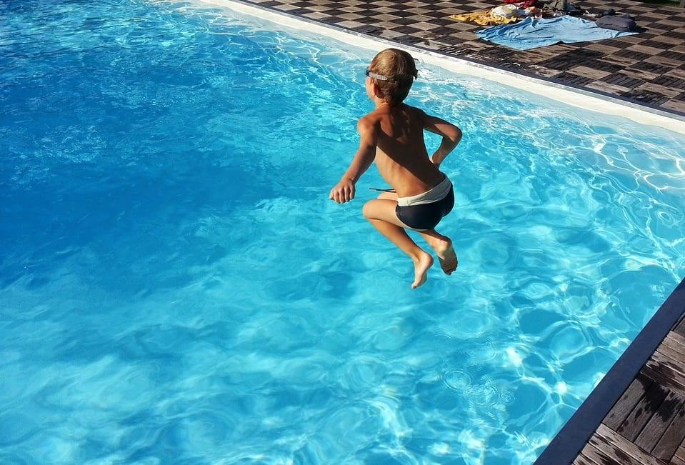 Niño saltando a la piscina.