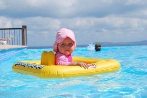 Bebé flotando sobre barca hinchable