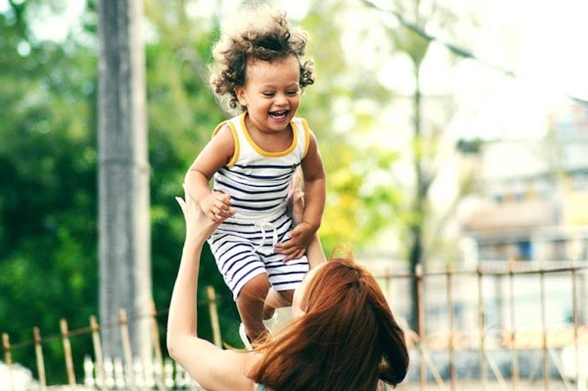 Una madre levantando al bebé en brazos
