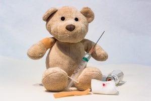Osito de peluche con inyección de vacuna.