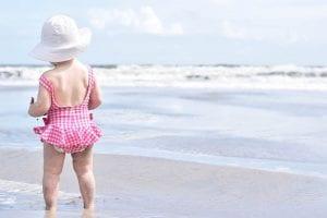 Niña bebé caminando por la orilla de la playa.