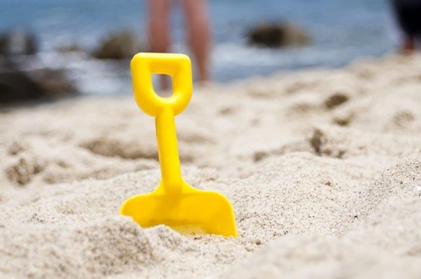 Pala enterrada en la playa de la arena