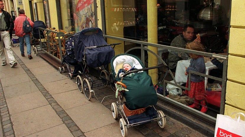 la siesta al aire libre de los bebés nórdicos carritos de bebé esperando fuera