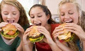 Adolescentes comiendo hamburguesas