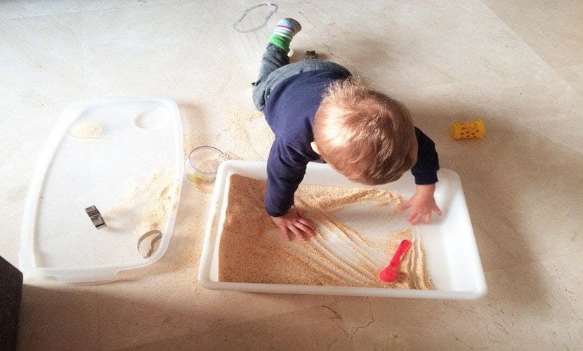 Niño jugando con bandeja de experimentación