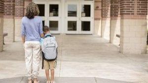 Madre y su hija en la entrada del colegio