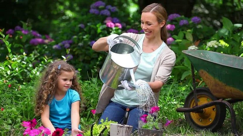 Una madre con su hija regando el jardín