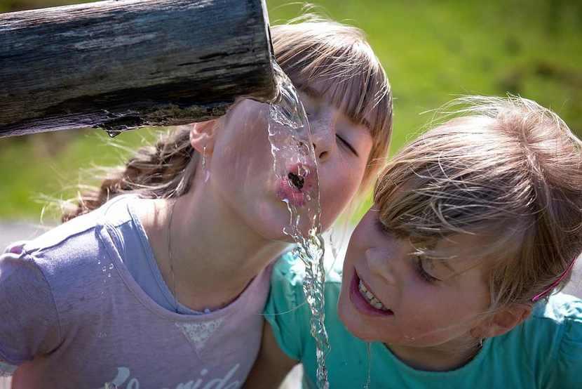 Niños bebiendo agua de una fuente