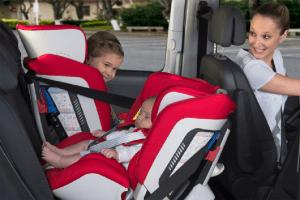 Madre en un coche con niños detras