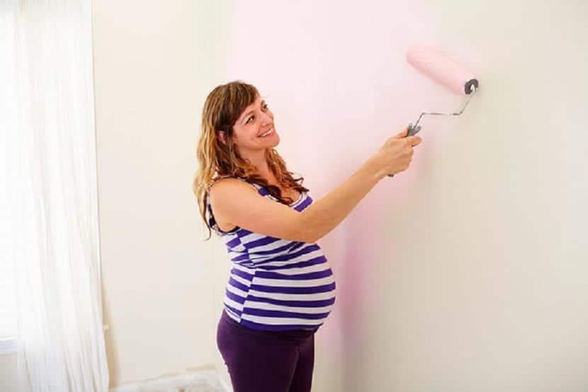 Mujer embarazada pintando el cuarto del bebé