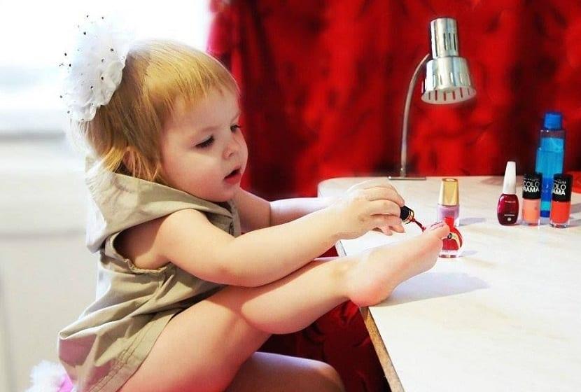 Niña pequeña pintándose las uñas