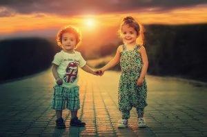 Dos niños se dan la mano mientras sonríen.