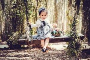 Niña pequeña columpiándose entre árboles