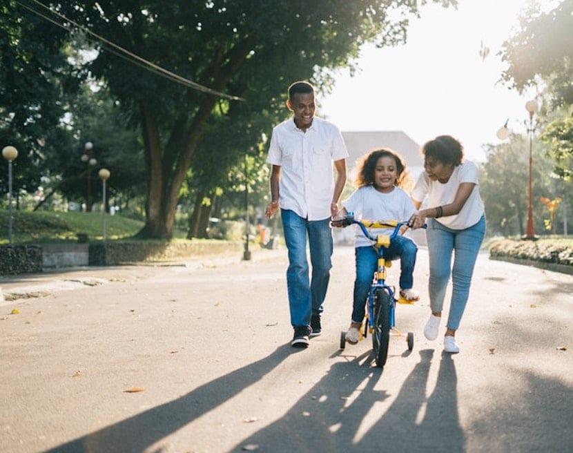 Niña montando en bicicleta ayudada por sus padres