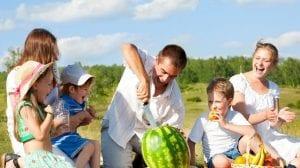 Familia comiendo fruta en el campo