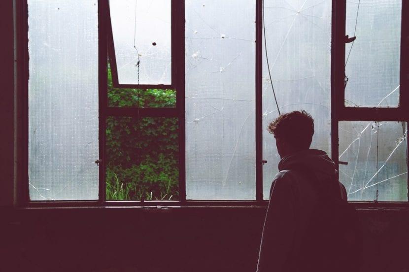 Joven mira a través de una ventana con inseguridad