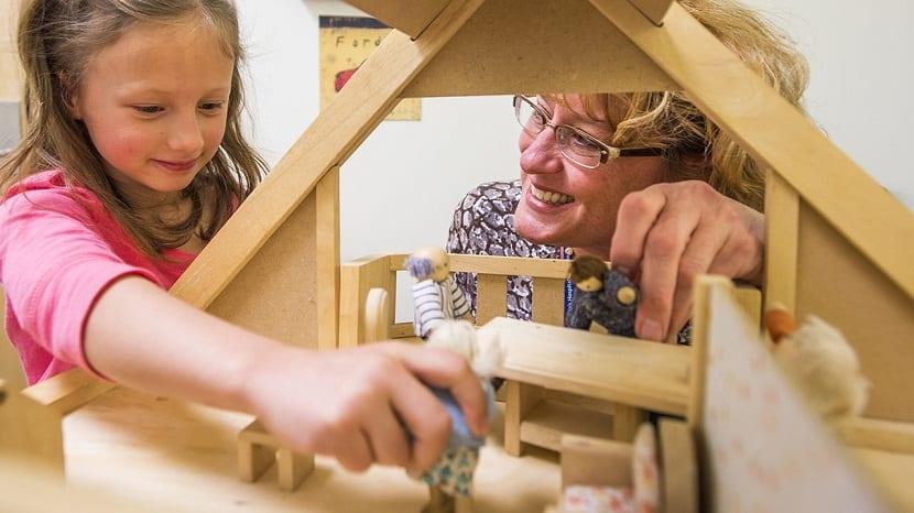 Madre e hija jugando con una casa de muñecas