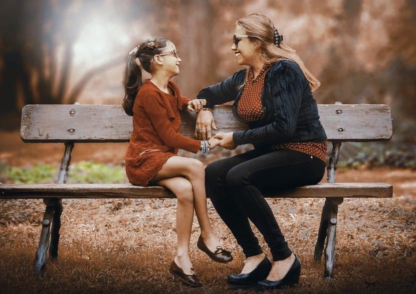 Madre e hija conversan en un banco del parque