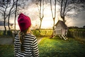 Niña mira hacia una casa que asocia con un hogar en la distancia.