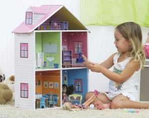 Niña jugando con una casa de muñecas
