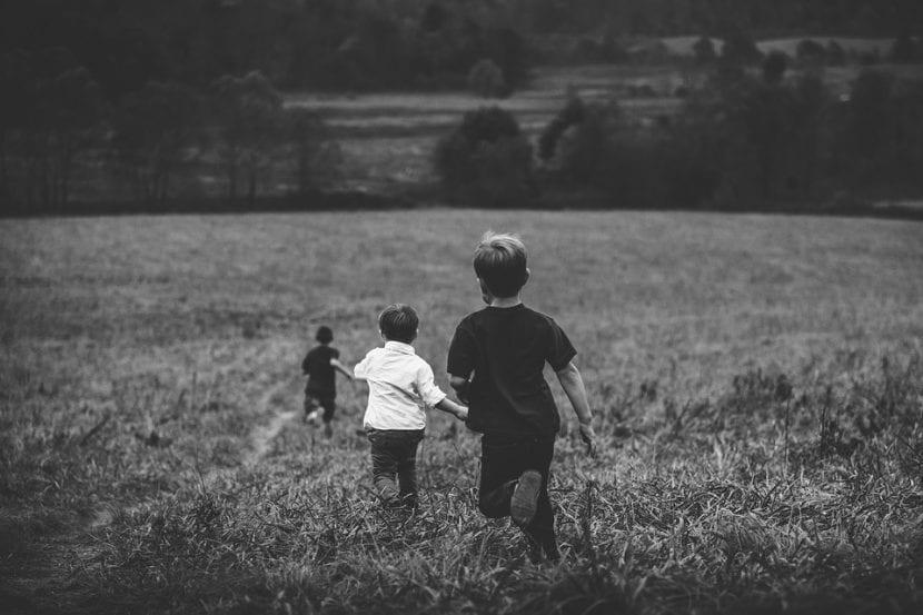 Niños corren jugando por el campo.