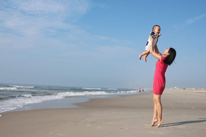Madre juega con su hijo en la playa