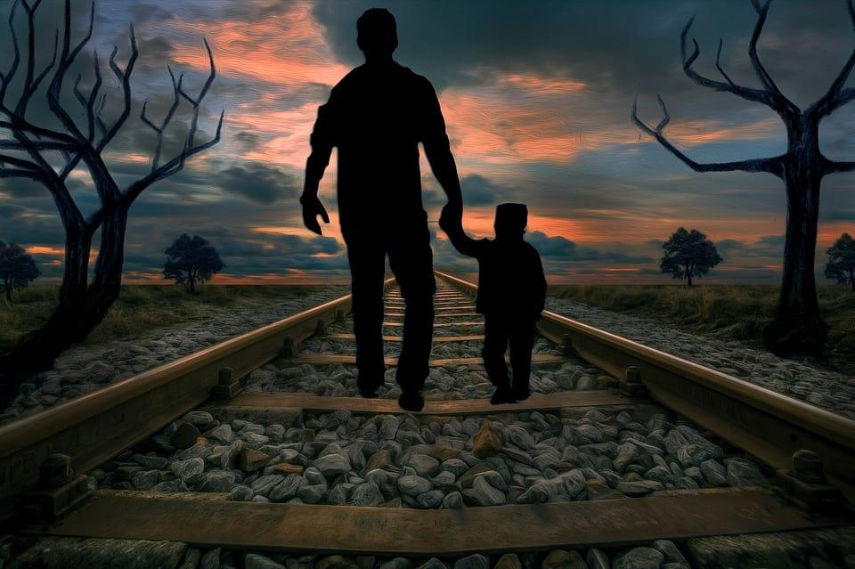Hombre se lleva a niño de la mano por una vía del tren
