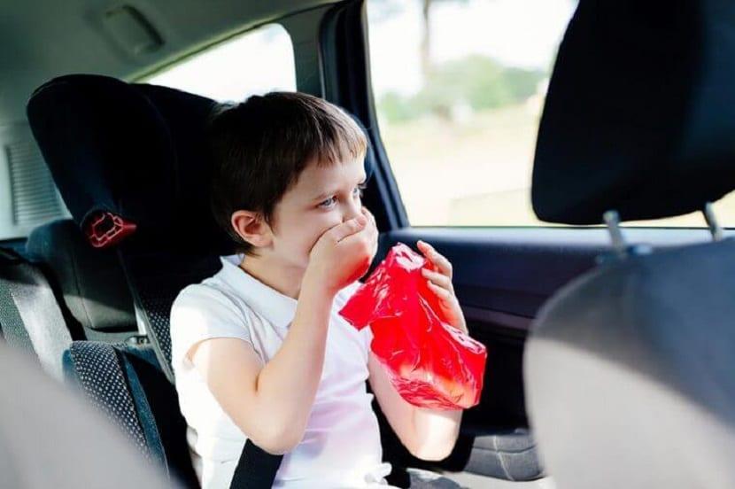 Niño vomitando en el coche