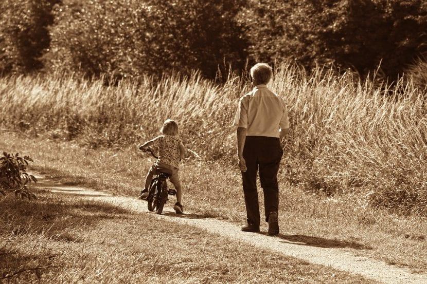 Abuelo con nieto en bicicleta paseando por el campo.