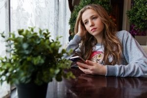 Chica adolescente está sola pensando en sus conflictos familiares y con el móvil en la mano.