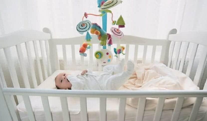 Bebé en la cuna mirando un móvil