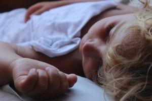 Niño tapado con una fina sábana logra dormirse con el calor.