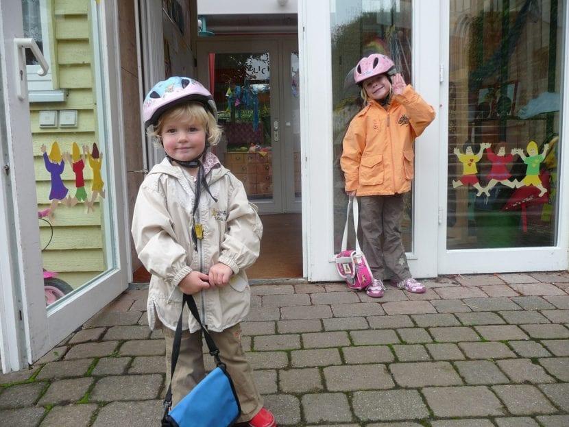 Niños en la entrada de su guardería con sus mochilas.