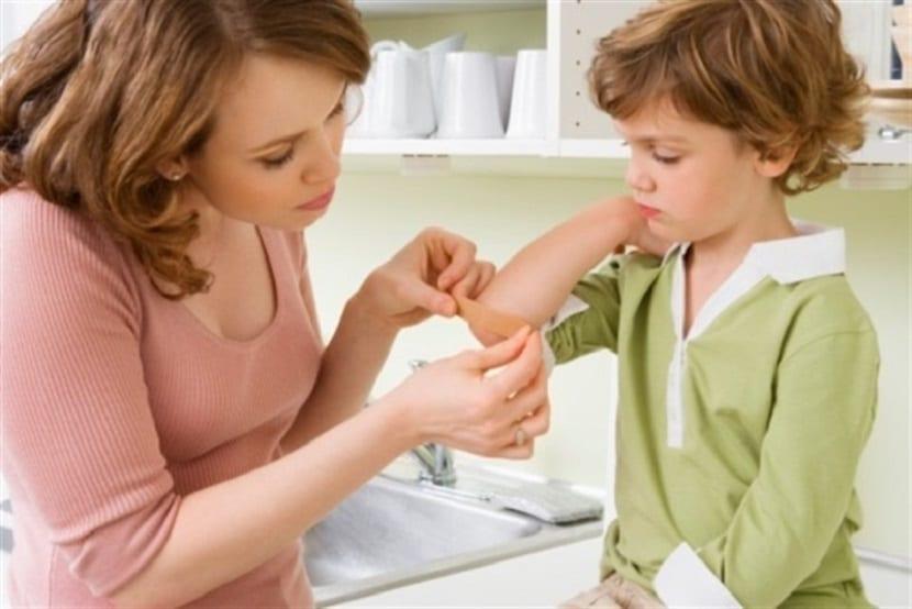 Madre curando una herida a un niño