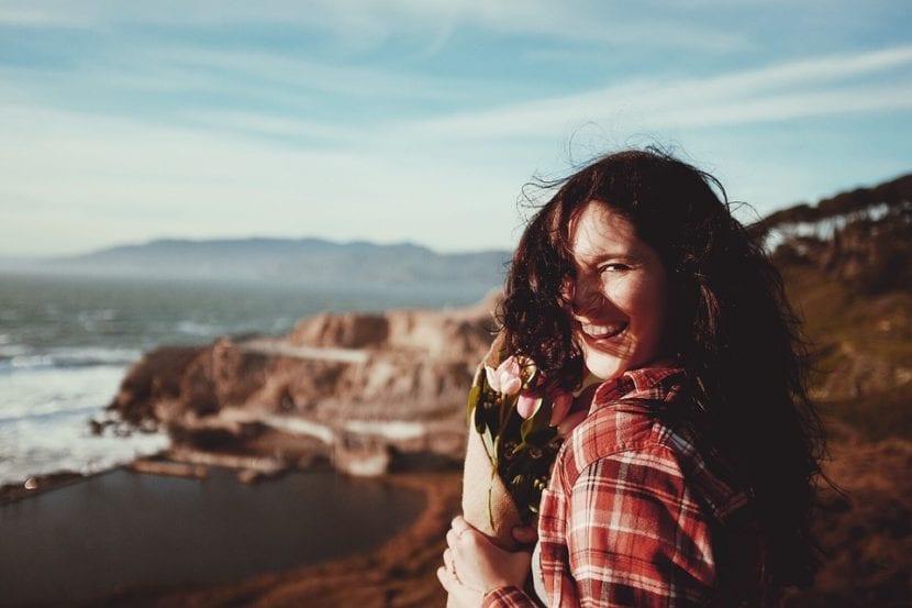 Mujer que sonríe frente al mar, es fotografiada por su pareja, que acaba de regalarle un ramo de flores.