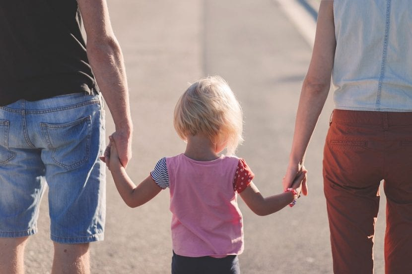 Niña paseando de la mano de sus padres.
