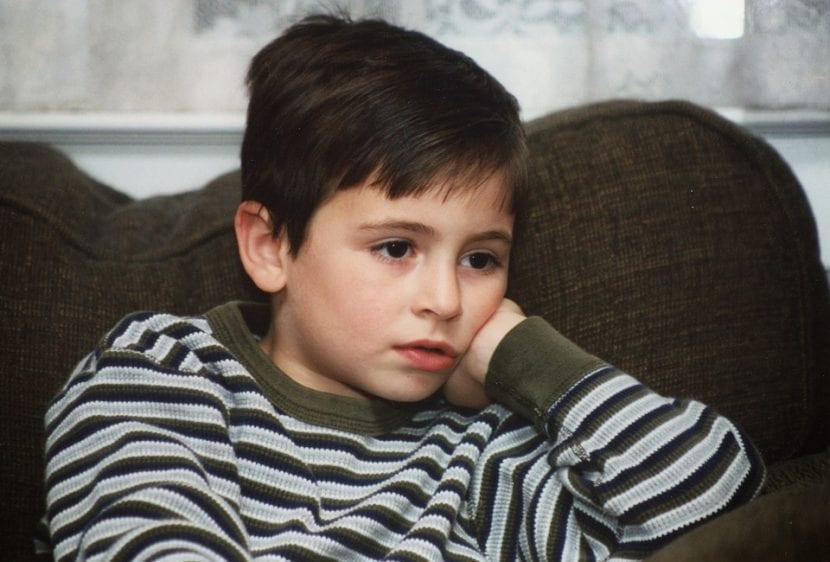 Niño solo, sentado en el sofá de su salón, viendo dibujos animados.