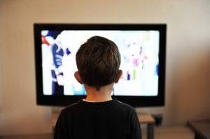 Niño absorto mirando un programa de televisión.