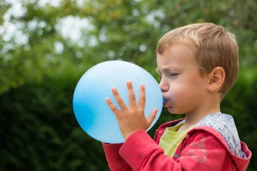 Un niño inflando un globo